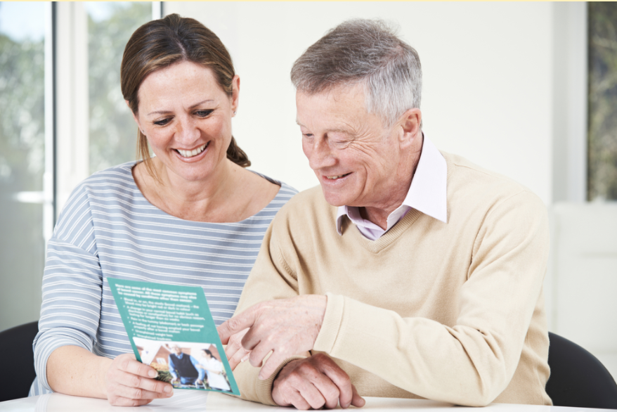 Adult daughter and senior father reviewing a brochure for an assisted living community.