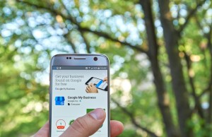 Hand holding up a mobile phone with Google My Business app highlighted