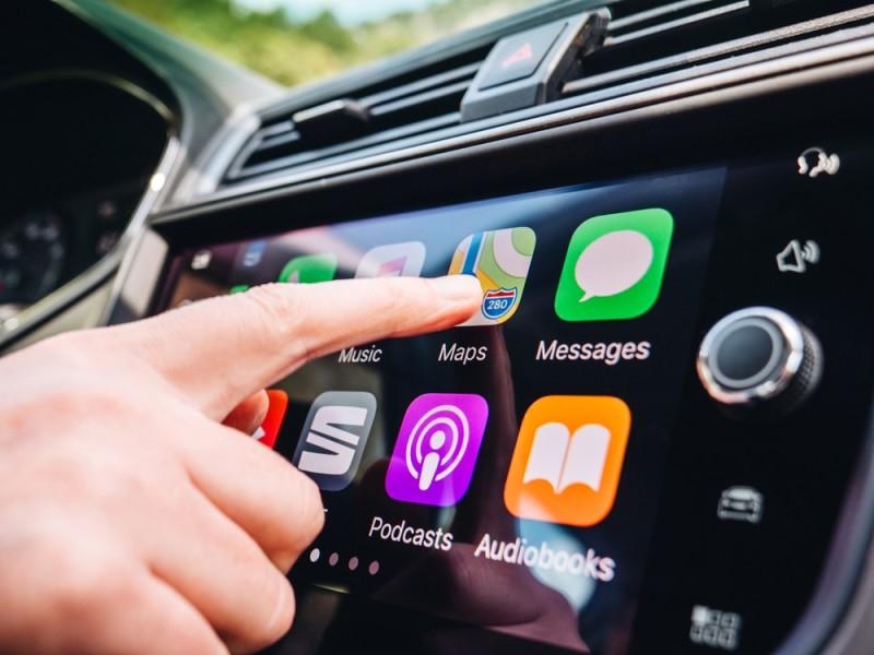 Woman pushing the Google Maps app on her car's Apple CarPlay dashboard.