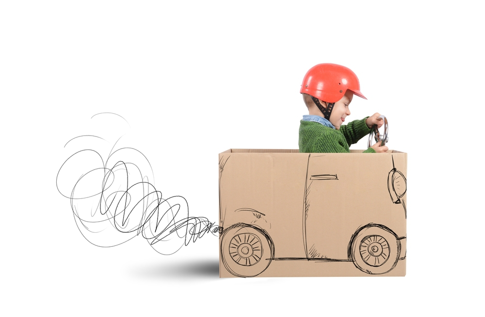 """Young boy driving a pretend car constructed from a cardboard box. Leverage Google Analytics and other tools to make content marketing decisions that will drive more traffic and increased engagement to your website."""