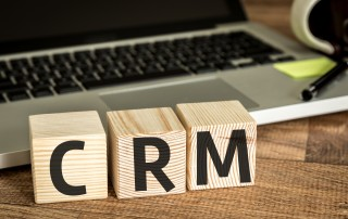 "Laptop keyboard behind three wooden blocks that have the letters ""CRM""."
