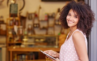 Female business owner with a tablet in hand recognizing the importance of a small business blog.