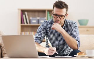 Young professional man working at home with a look of concentration on his face, computer in front of him, holding a pen in his hand.