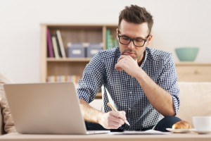 Image of a young professional man concentrating in front of a laptop with a pen in his hand, working at home.