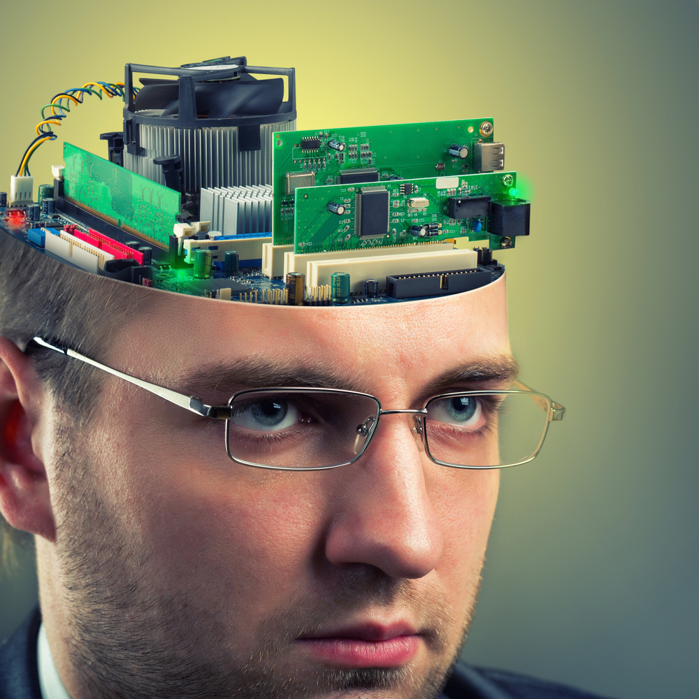 Confident businessman with computer in head representing how closely humans and machines work together.