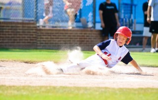 Youth baseball player sliding home. Website homepage sliders are loved by clients but can be detrimental to website usability and conversions.