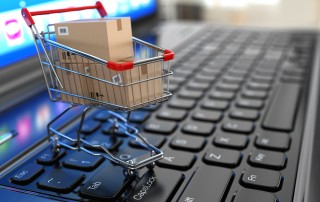 Tiny shopping cart with cardboard boxes on top of laptop keyboard signifying Ecommerce