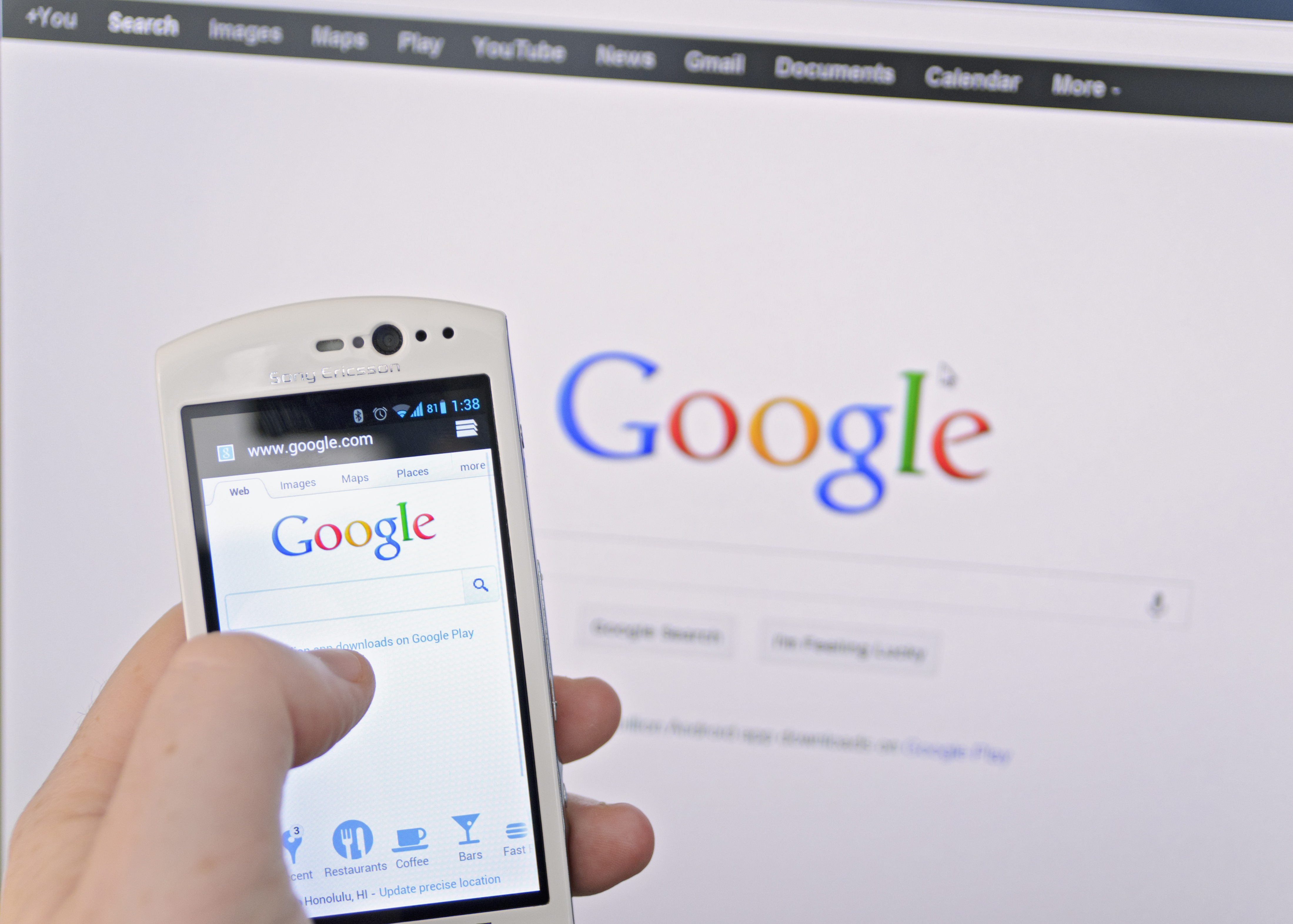 Image of a person on a smartphone conducting a Google search on a phone in front of a computer showing Google on screen.