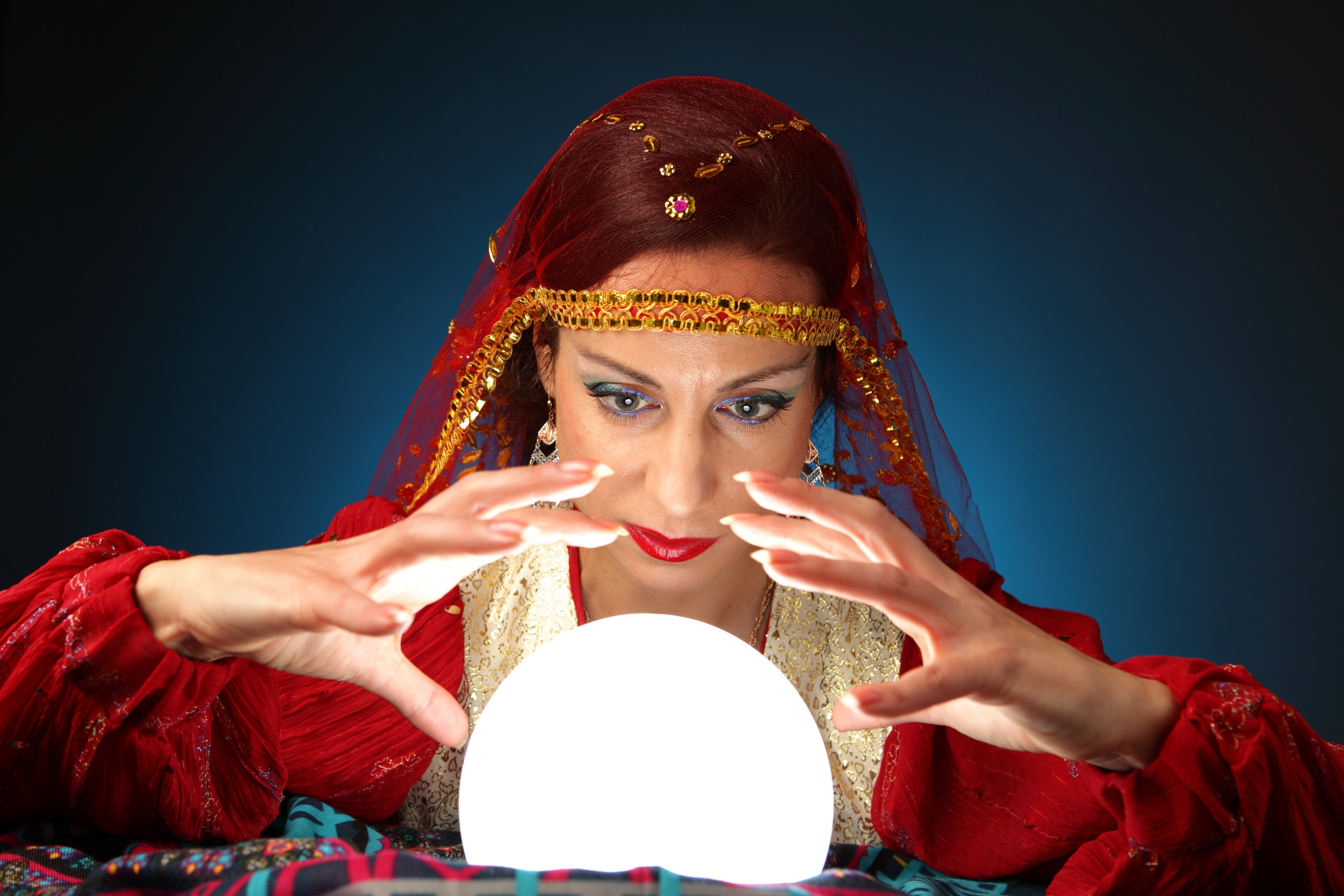 Woman dressed in fortune-tellers costume peering into a lighted crystal ball.