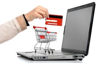Laptop with small shopping cart and a hand with credit card symbolizing online shopping.