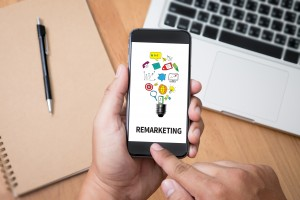 """Image showing hands swiping on a smartphone that says """"Remarketing"""" with a laptop and folder in background."""