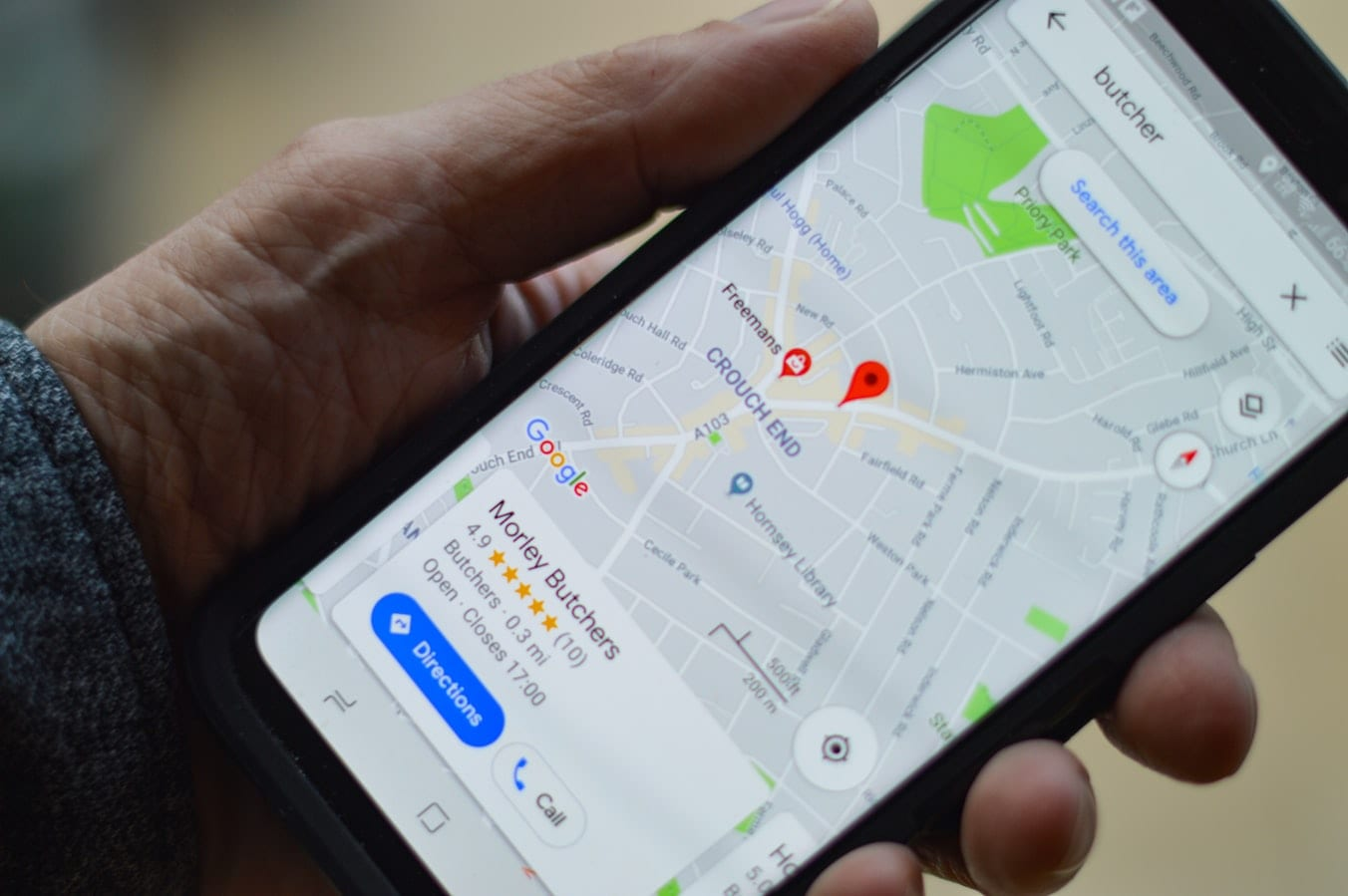 Image of hand holding a smartphone with Google Maps open represents local SEO.