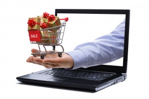 Man's hand holding tiny shopping cart full of holiday gifts through a laptop screen representing holiday digital marketing.