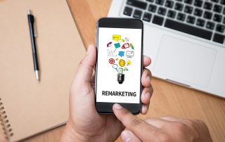 "Image showing hands swiping on a smartphone that says ""Remarketing"" with a laptop and folder in background."
