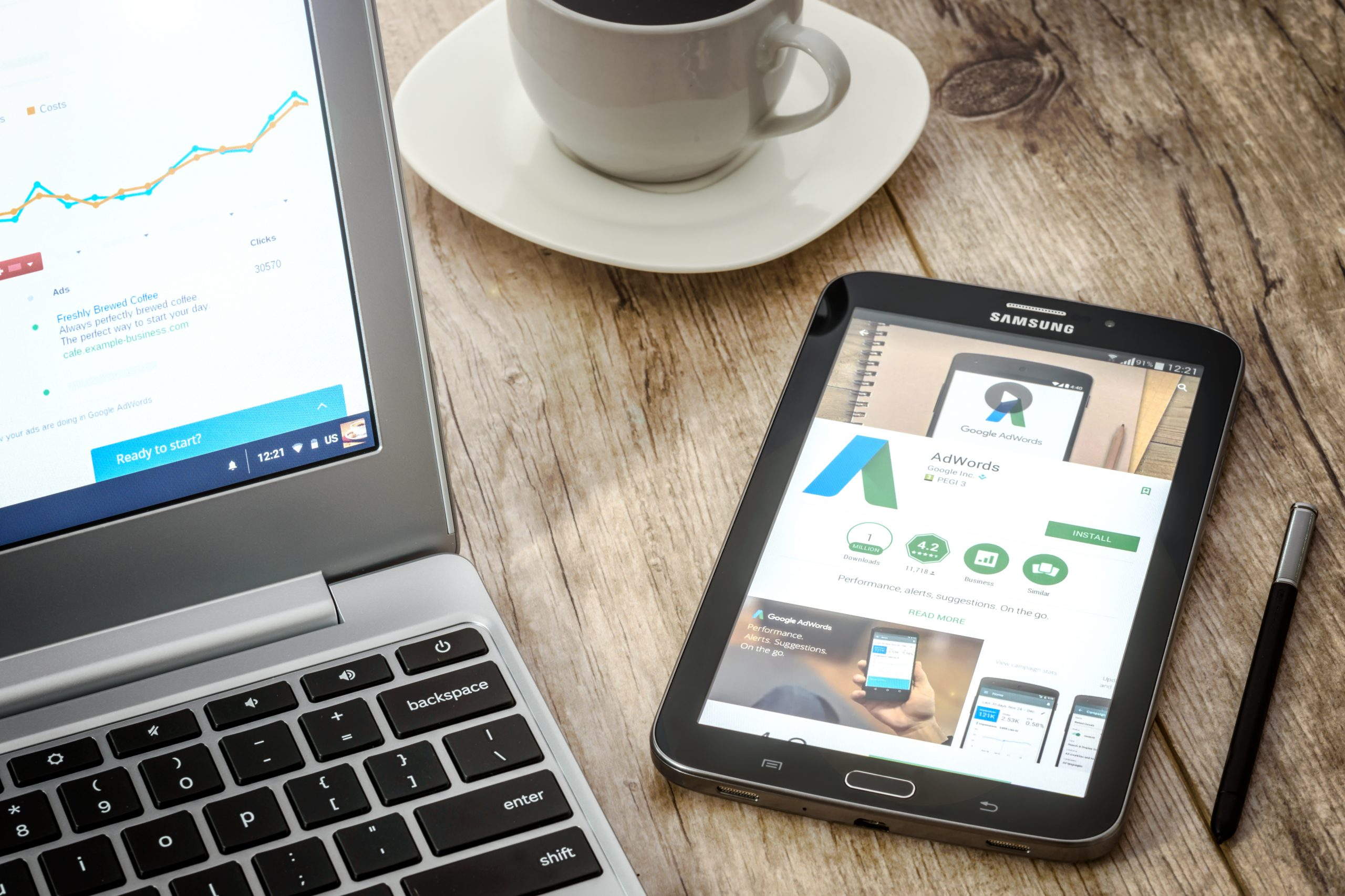 Tablet on desk shows Google Ads site.