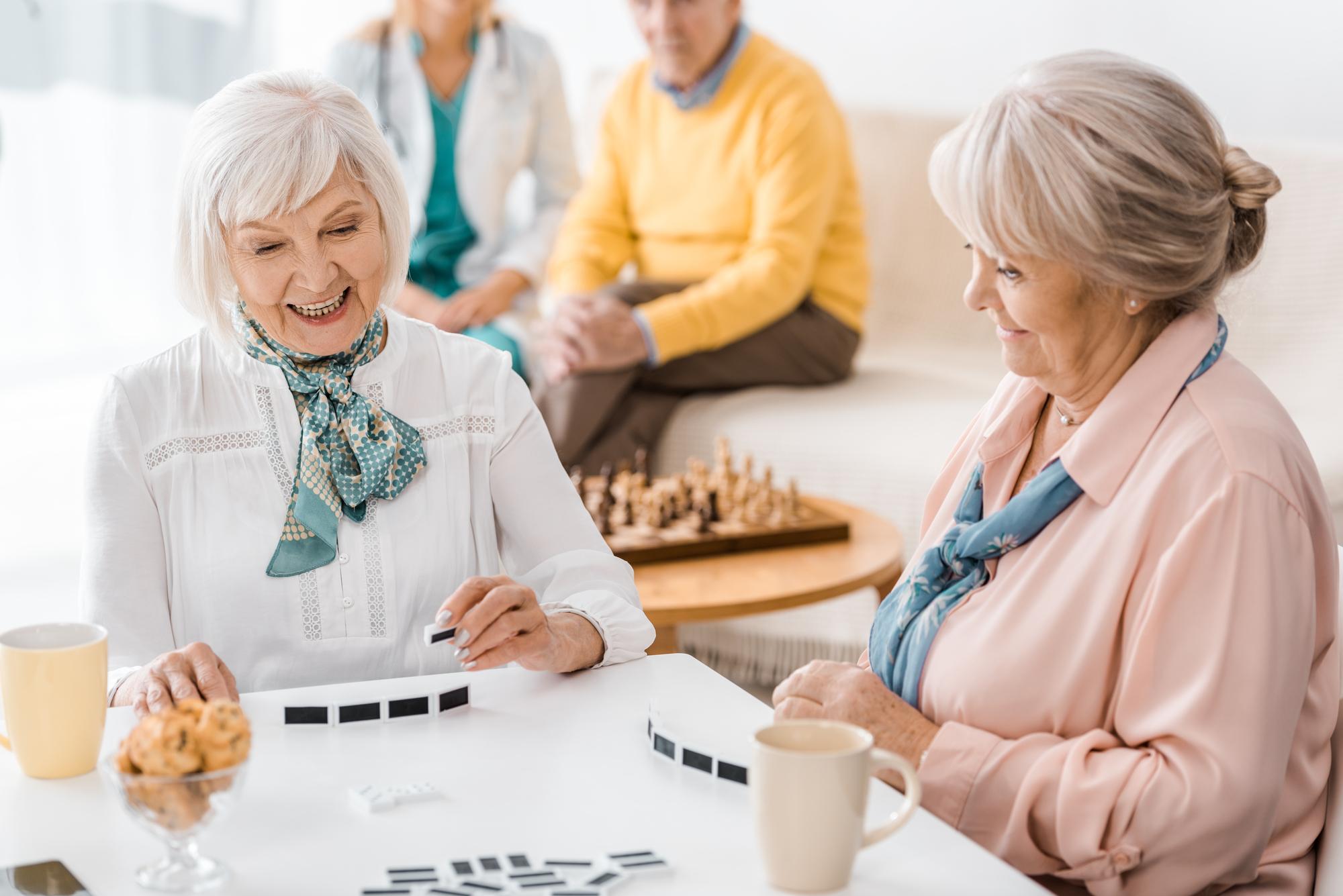 Seniors enjoying tea and dominos in a luxury senior living coommunity
