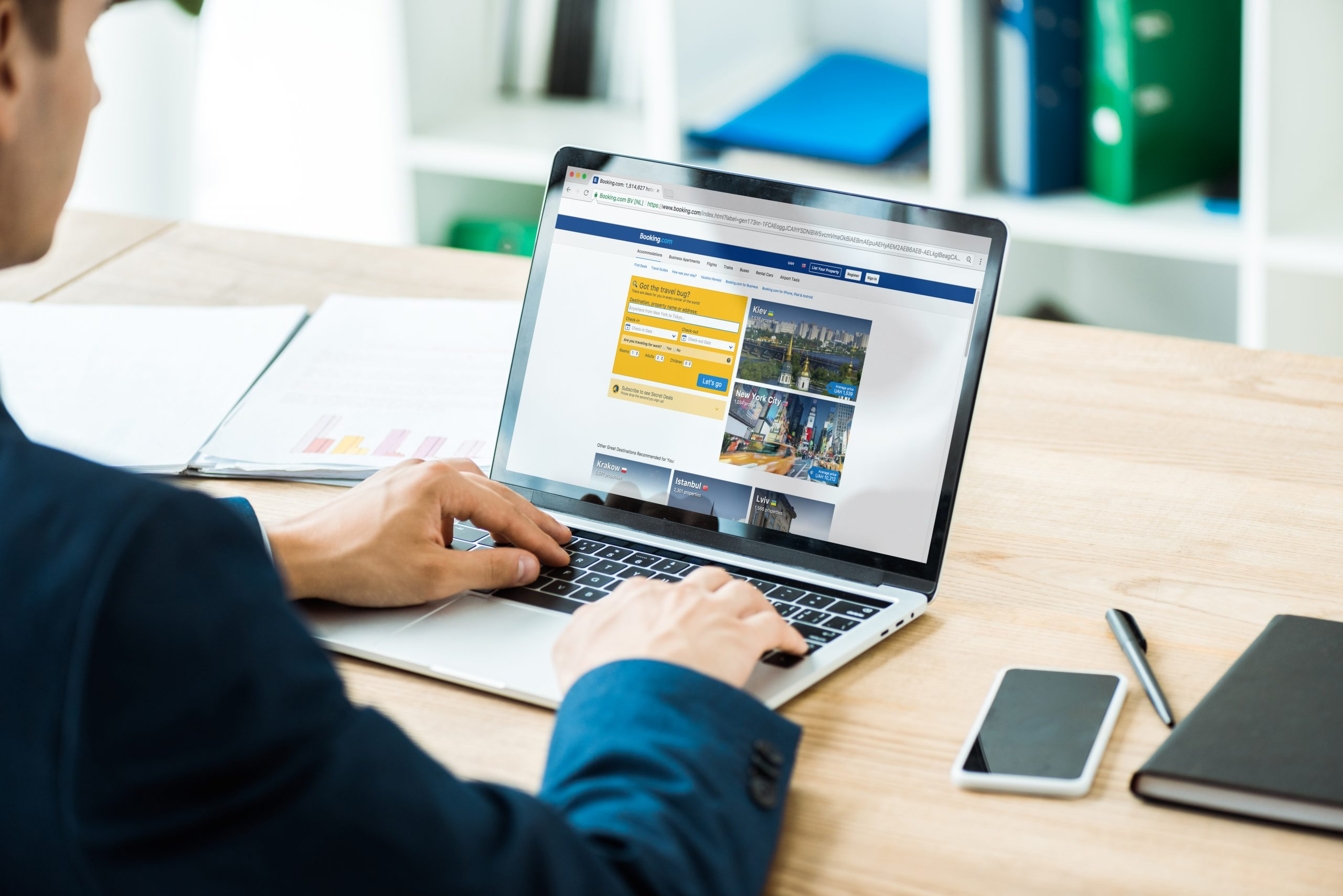 Digital marketer at desk, working on laptop