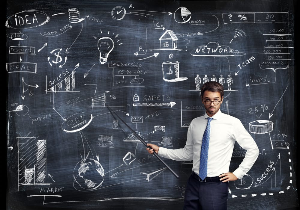 Image of teacher in front of blackboard to represent the task of getting small business owners to understand digital marketing