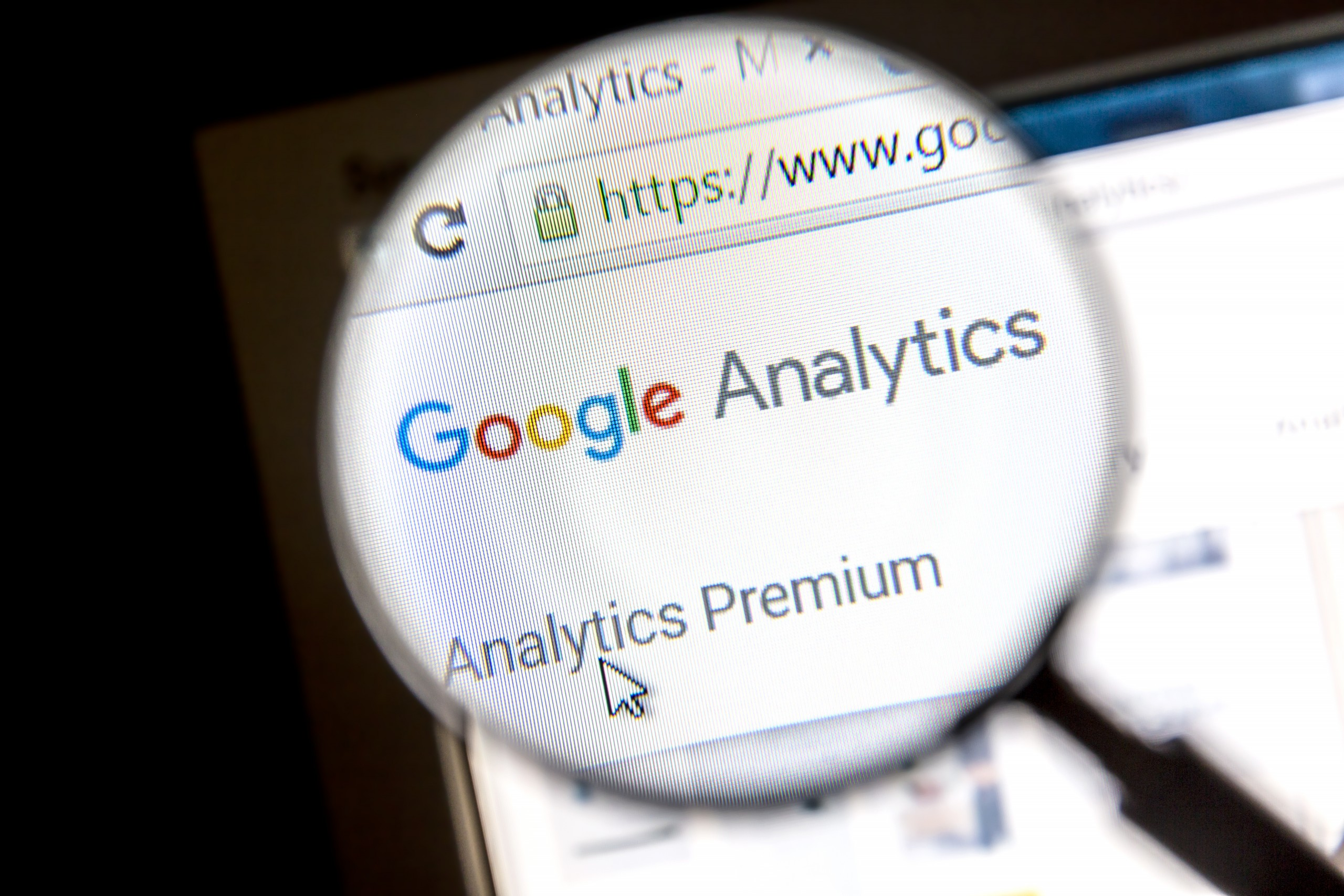 Magnifying glass showing Google Analytics Analytics Premium on computer screen signifying Google Analytics For Small Businesses.