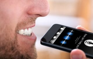 Close-up Of A Happy Man Using Voice Recognition Function On Mobile Phone symbolizing optimizing for voice search