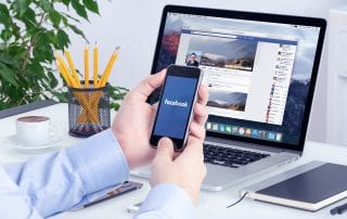 Small business owner at a desk using Facebook on his mobile device and laptop which represents Facebook retargeting.