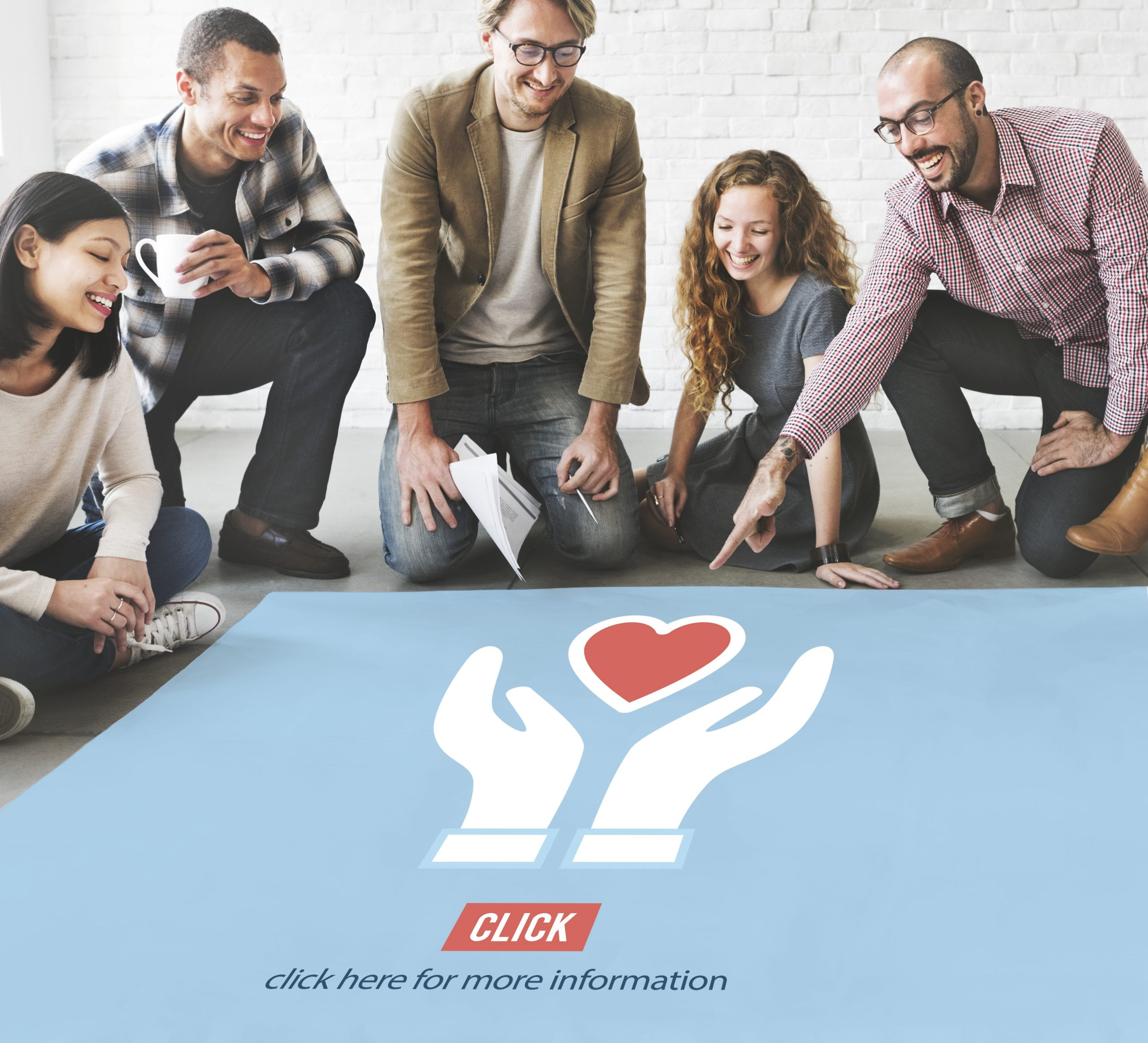 Diverse group of people surrounding a poster with hands and a heart symbolizing nonprofit digital marketing.